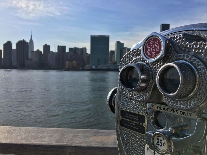 Close-up of coin-operated binocular by hudson river against sky in city