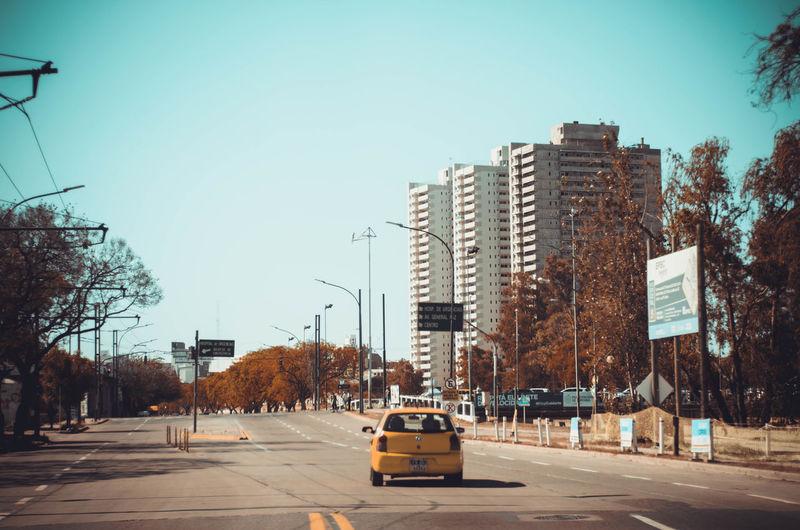 Cars on city street by buildings against clear sky