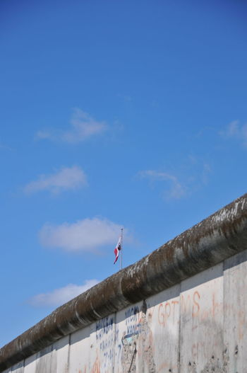 Low angle view of bird on wall against blue sky