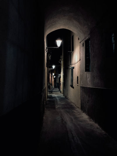 Empty narrow alley along buildings at night