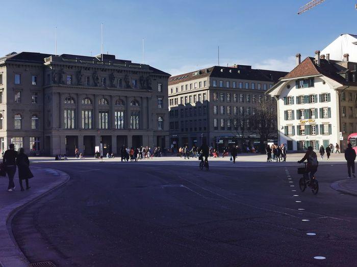 People walking on road by buildings in city
