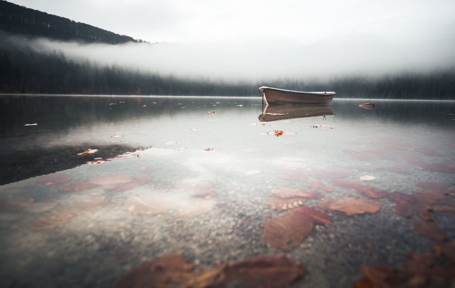 Water Cold Temperature Nature Winter Lake Tranquil Scene Day Scenics - Nature Tranquility Beauty In Nature No People Fog Reflection Sky Non-urban Scene Frozen Transportation Outdoors Surface Level Nautical Vessel Floating On Water Leaves Fall Beauty Reflection Moody