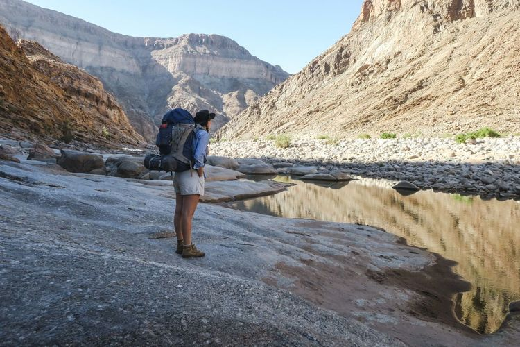 Female hiker standing next to river in scenic canyon Adventure Backpack Bag Beauty In Nature Exploration Explore Hike Hiker Hiking Leisure Activity Mountain Mountain Range Nature Nature One Person Outdoor Outdoor Photography Outdoors River Rugged Scenics Travel Wild Wilderness Women
