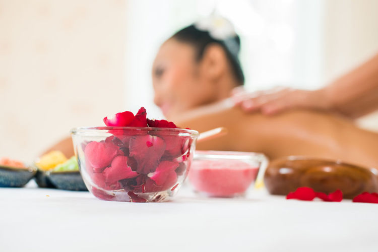 Close-Up Of Petals In Bowl With Cropped Hands Of Masseuse Giving Massage To Young Woman Relaxing At Spa