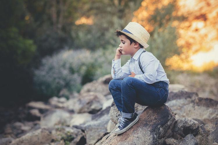 Cute boy wearing hat looking away while sitting on rock