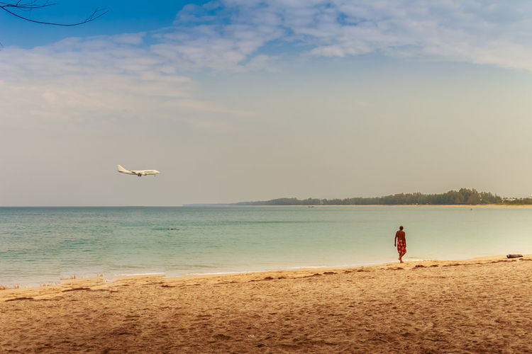 Unidentified tourists and the beautiful seascape view of Naiyang beach while the airplane landing at Phuket international airport, Phuket Province, Thailand. Landing NaiYang NaiyangBeach Phuket Phuket Island Phuket Thailand Phuket International Airport Phuket Travel Phuket, Thailand Phuket,Thailand Tourist Tourist Attraction  Airplane Airport Beach Beauty In Nature Bird Day Flying Full Length Horizon Over Water International Airport Landing Plane Men Nature One Person Outdoors People Real People Scenics Sea Sea And Sky Seascape Sky Standing Tourist Destination Vacations Water
