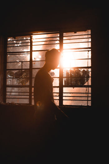 Sunlight streaming through silhouette man standing against window at sunset