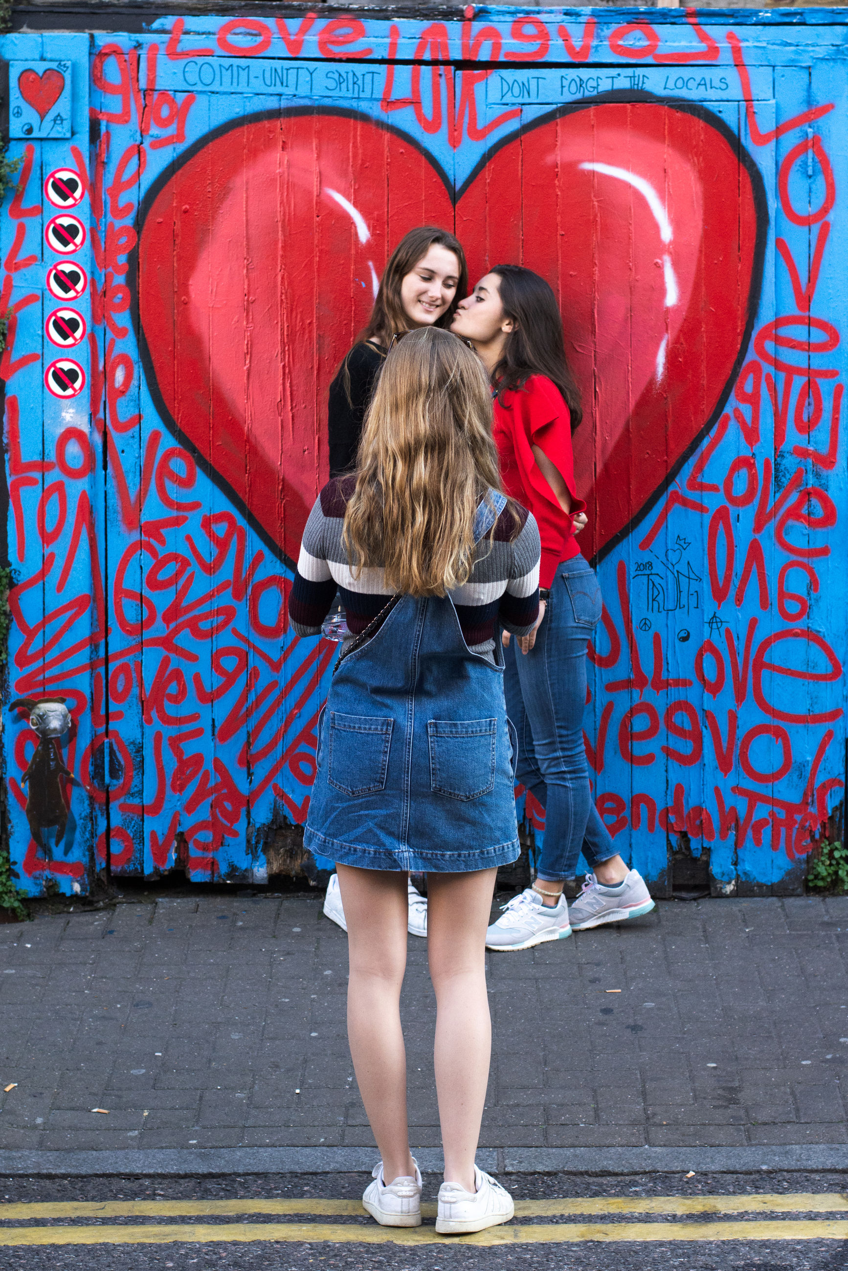 full length, togetherness, young women, young adult, emotion, standing, smiling, happiness, two people, women, love, looking at camera, adult, front view, casual clothing, graffiti, portrait, day, positive emotion, people, outdoors, hairstyle