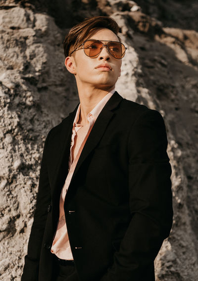Young man wearing sunglasses standing on rock