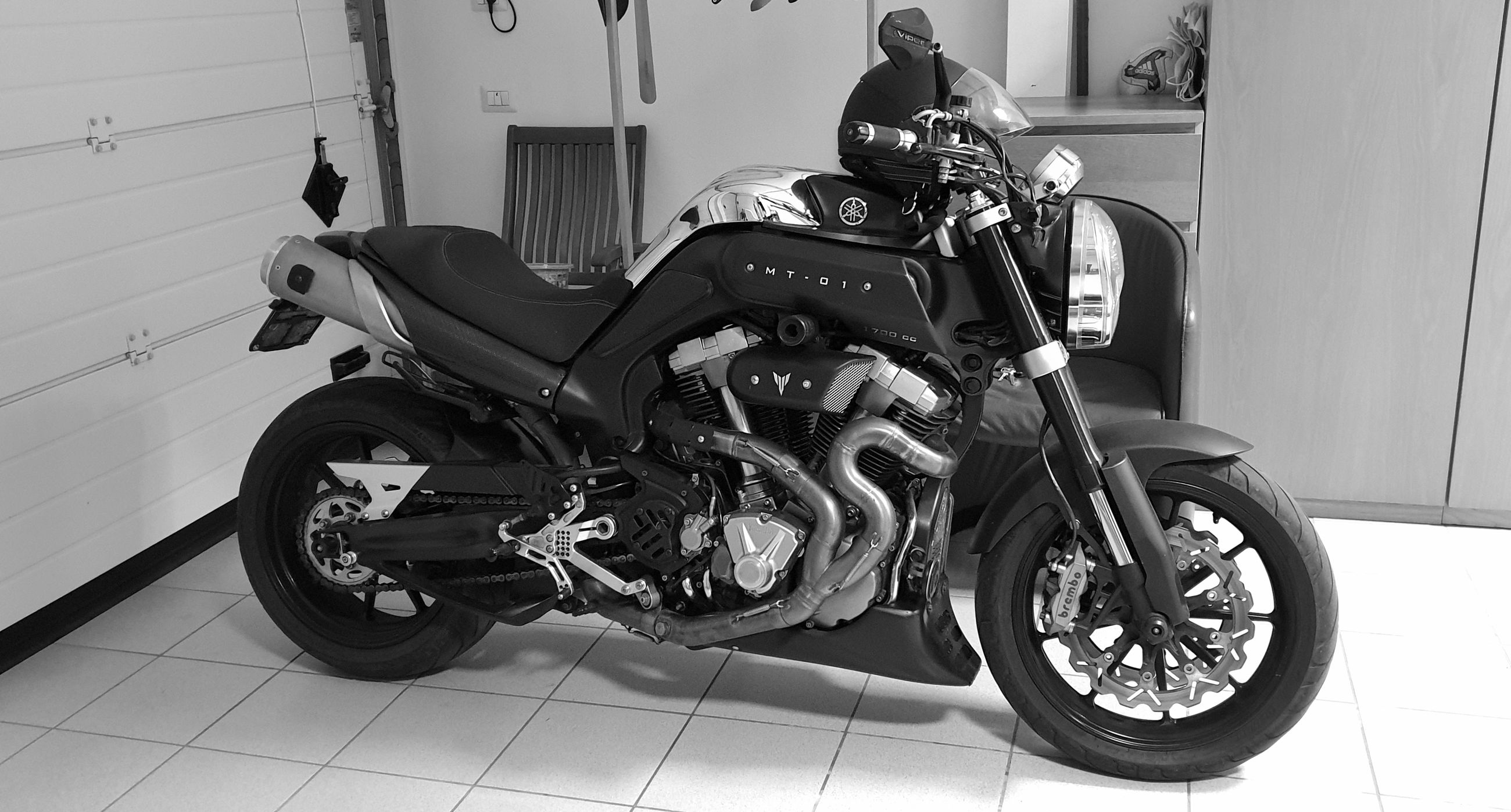 transportation, mode of transportation, motorcycle, land vehicle, scooter, one person, flooring, day, city, stationary, street, motor scooter, lifestyles, side view, wheel, indoors, tile, real people, tiled floor, luxury