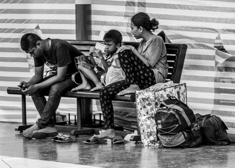 Sitting at bench Bag Baggage Bench Black & White My Commute-2016 EyeEm Photography Awards Boy Casual Clothing Child City Life The Portraitist - 2016 EyeEm Awards The Street Photographer - 2016 EyeEm Awards Family Leisure Activity Life Lifestyles Rest My Commute Sitting Station Talking Teenager Train Station Wait Waiting Women