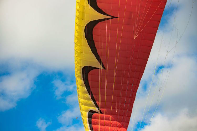 Low angle view of paragliding canopy against sky