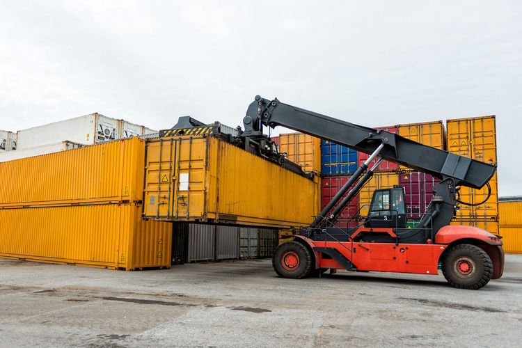 Mobile stacker handler in action at a container terminal. Harbor Cargo Container Day Export Freight Transportation Import Industry Logistic No People Outdoors Shipping  Sky Terminal Transfer Transportation