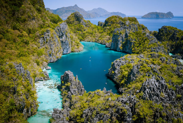 El Nido, Palawan, Philippines. Aerial drone view of beautiful big lagoon surrounded by karst limestone cliffs. Tourists explore area on kayaks. Miniloc Philippines Palawan Lagoon Beautiful Aerial View Limestone Island El Nido Travel Landscape Nature Paradise Tourist Water Archipelago Boat Jungle Mountain Natural Outdoor Scenery Scenic Summer Sunny Tropical Vacation Karst Blue Ocean Bay Big Lagoon Sand Sea Shore Tour A Background Beach Relax Seascape Sky Tropic ASIA Tourism Asian  Small Lagoon BIG Clouds Idyllic