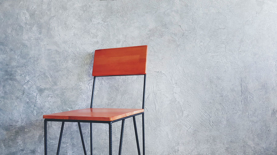 Close-up of red chair on table against wall