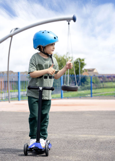 Full length of boy gesturing while standing on push scooter