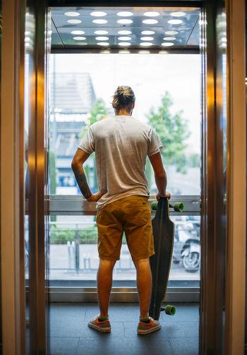 Rear view of man standing against door