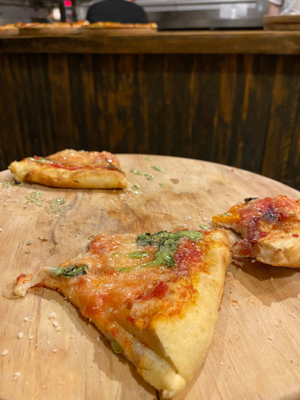 CLOSE-UP OF PIZZA ON CUTTING BOARD ON TABLE