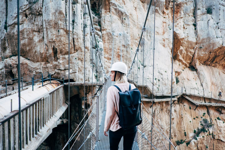 Rear view of young woman walking on rope bridge against rock