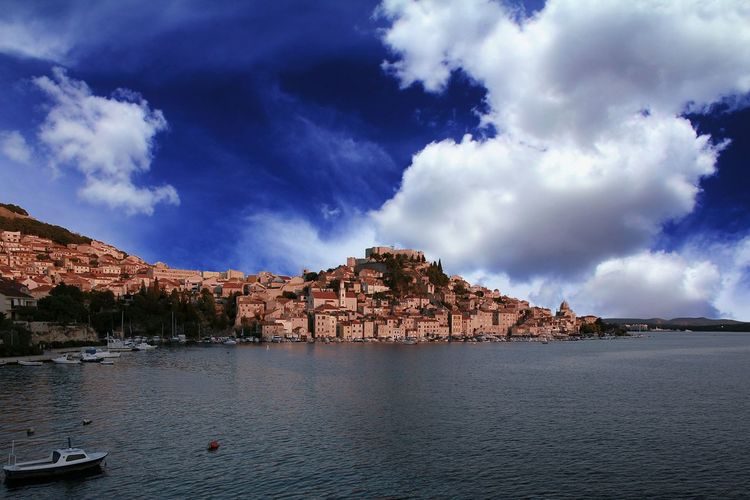 Scenic view of sea by townscape against cloudy sky