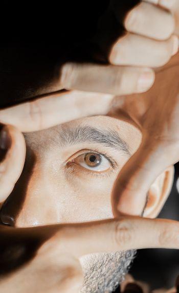 Close-up of man eye through finger frame