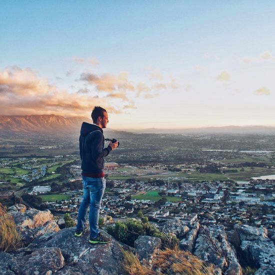 Young man standing on rock formation overlooking city against sky during sunset