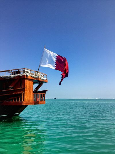 Flag Waving On Traditional Boat Over Sea Against Clear Sky