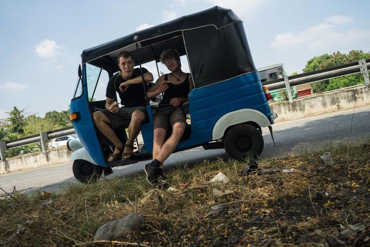 Portrait of friends sitting on jinrikisha on road