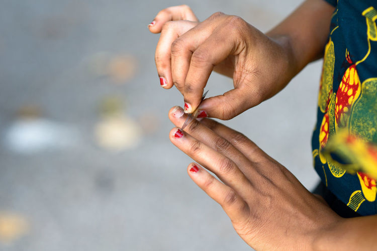 Midsection of woman removing red nail polish