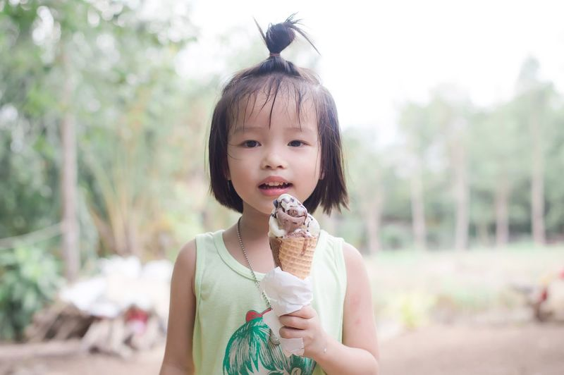 Portrait of cute girl eating ice cream while standing outdoors