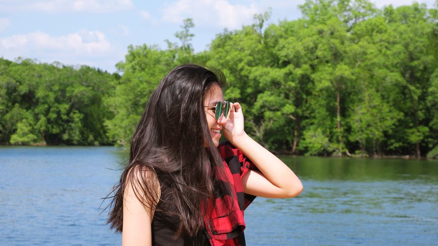 Portrait of beautiful young woman holding plants against lake