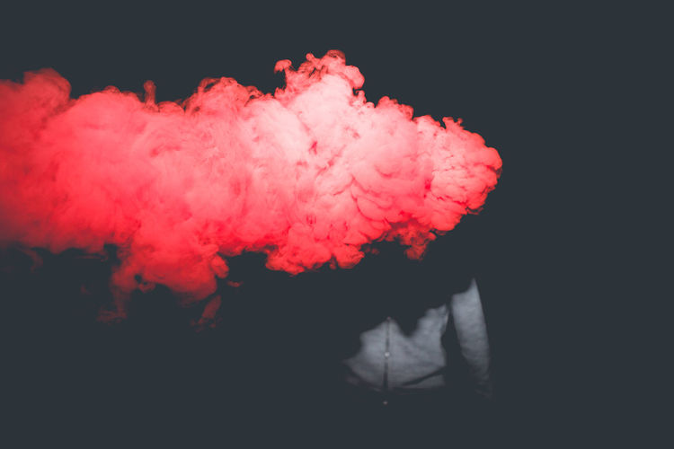 Smoke by man standing against black background