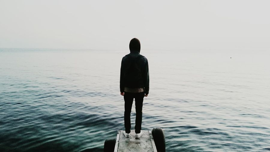 Rear view of man standing by sea