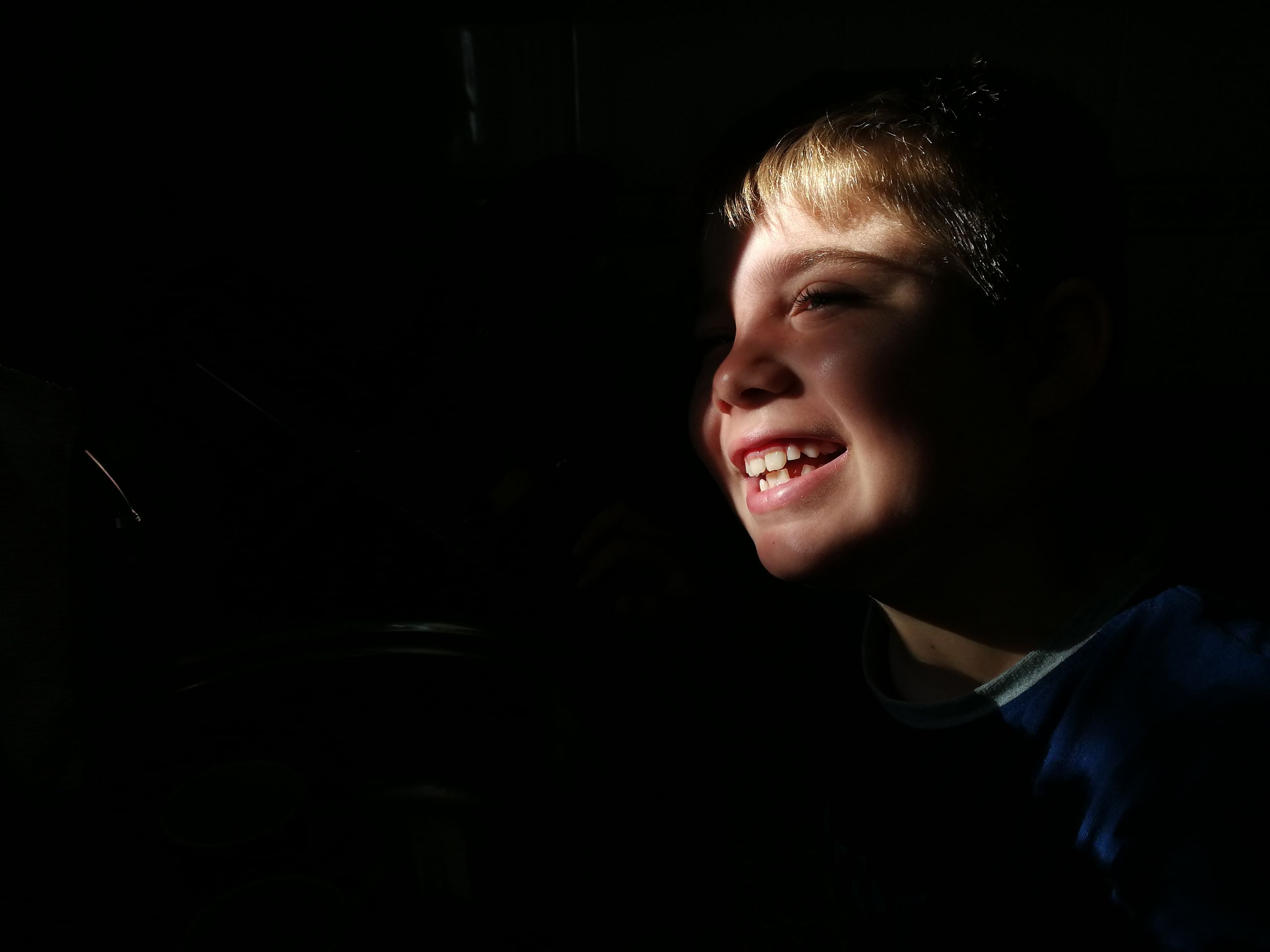 smiling, happiness, one person, indoors, real people, cheerful, boys, black background, childhood, night, young adult, close-up, people