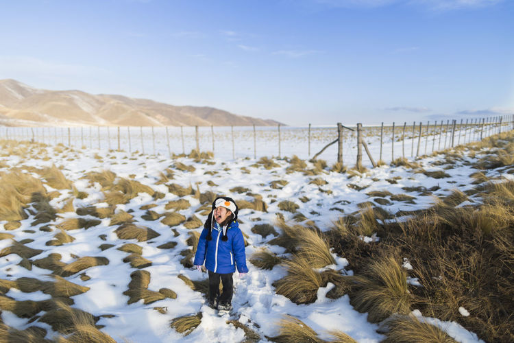 Full length of girl screaming while standing on snow covered field during winter