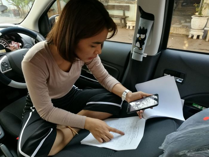 girl Leisure Activity Motor Vehicle Car Land Vehicle Travel Publication Hairstyle Mode Of Transportation Real People Transportation Holding Three Quarter Length Women One Person Sitting Lifestyles Indoors  Casual Clothing Vehicle Interior