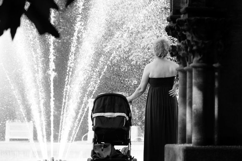 Rear View Of Woman Standing With Baby Carriage Against Fountain