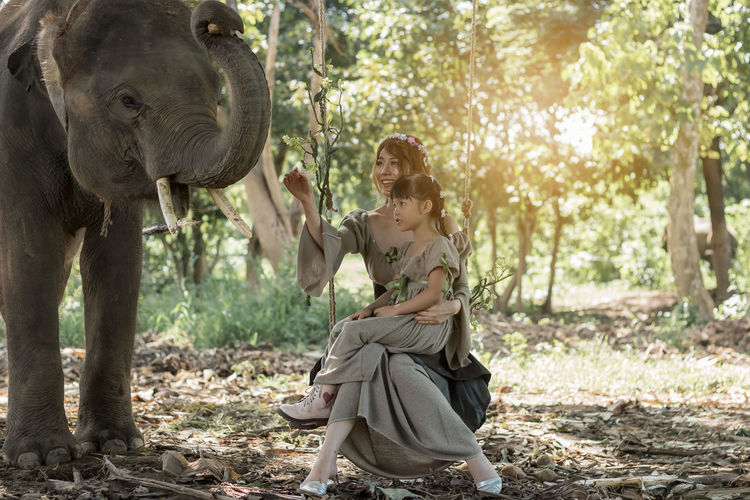 Woman with daughter touching elephant in forest