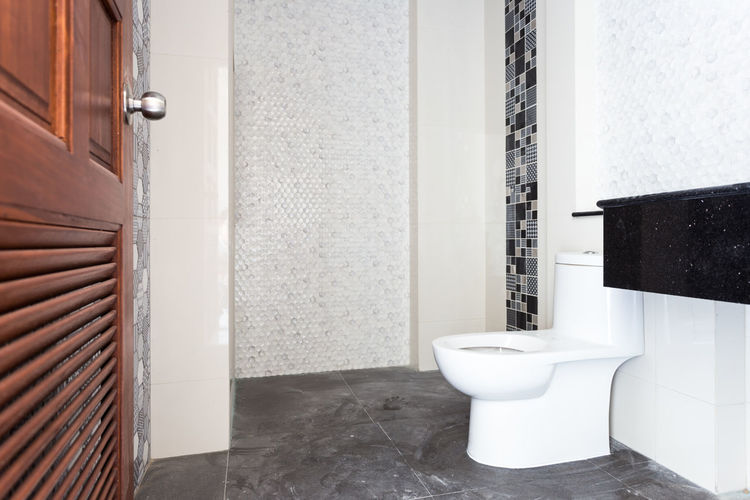 Architecture Bathroom Built Structure Day Domestic Bathroom Domestic Room Door Entrance Flooring Flushing Toilet Home Home Interior Home Showcase Interior Hygiene Indoors  Luxury Modern No People Seat Tiled Floor Toilet Toilet Bowl White Color