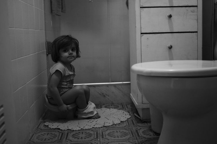 Portrait of girl sitting in bathroom