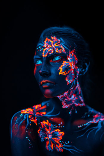 Close-up of woman with illuminated body paint against black background