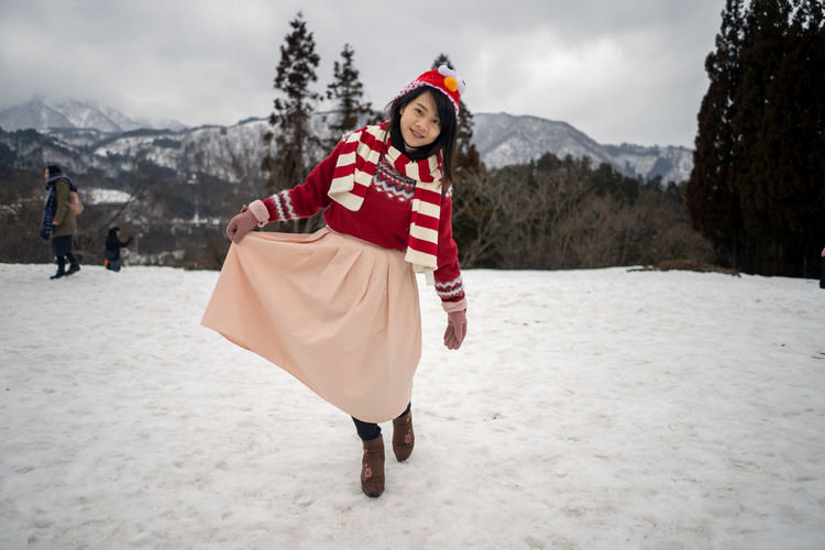 Portrait of young woman walking on snow against mountains and sky