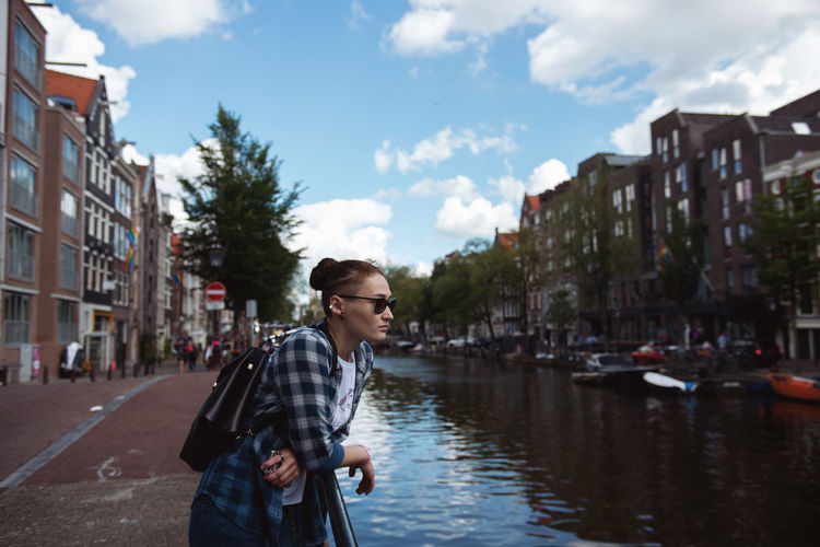 Man standing by canal in city against sky