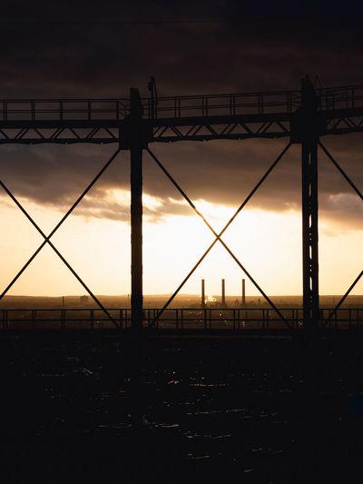 Silhouette bridge against sky during sunset