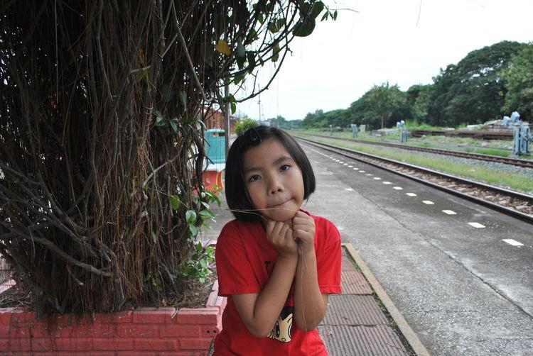 Portrait of girl sitting on railroad station platform