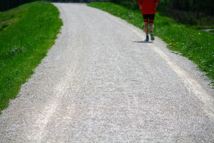 Rear view of person jogging on road