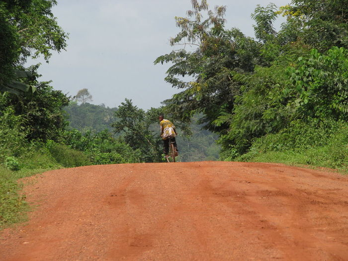 Rear view of man looking over shoulder while riding bicycle on dirt road at field