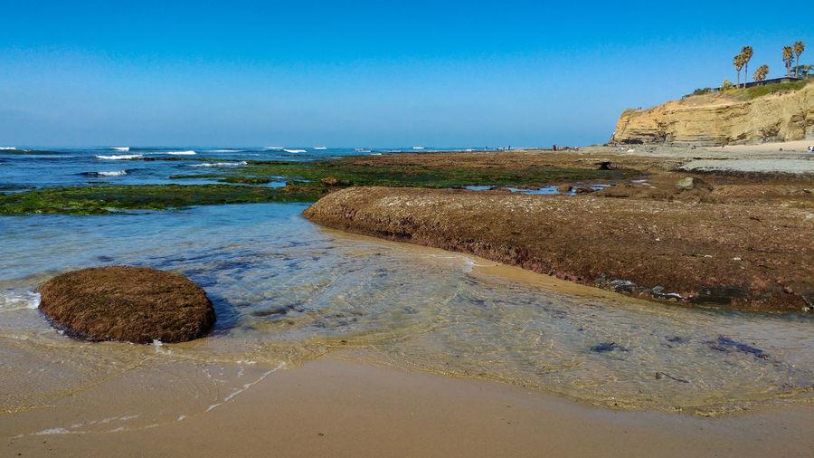 Rocks on beach against clear blue sky
