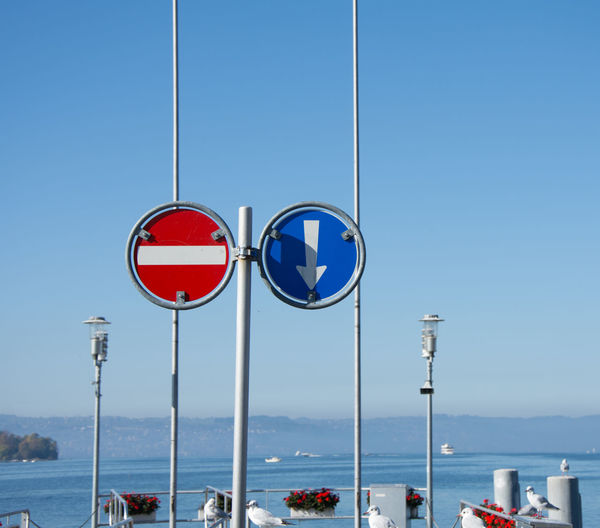 Road sign by sea against clear blue sky