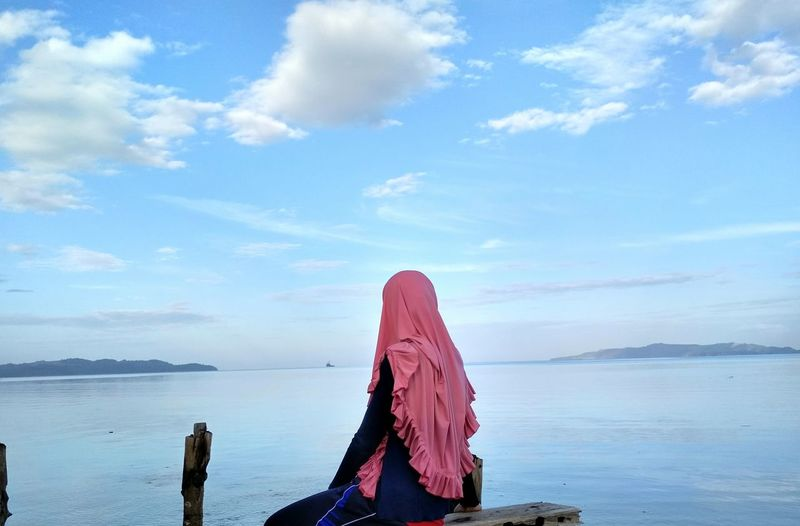 Woman in hijab looking at sea against sky